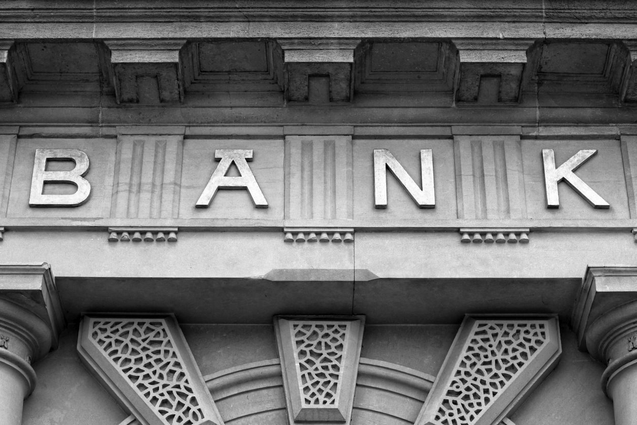 Embossed letters spell bank above the door of financial building